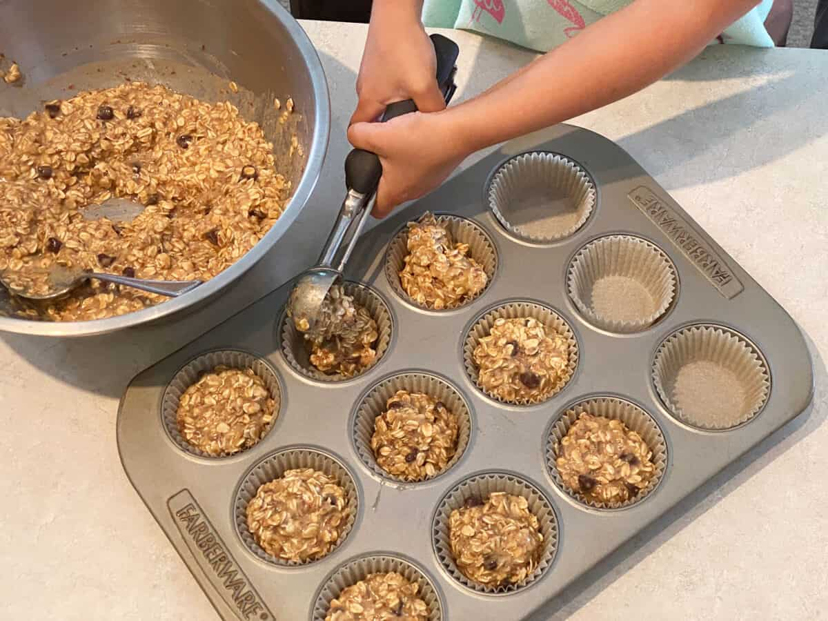 Filling a muffin tin with oatmeal batter
