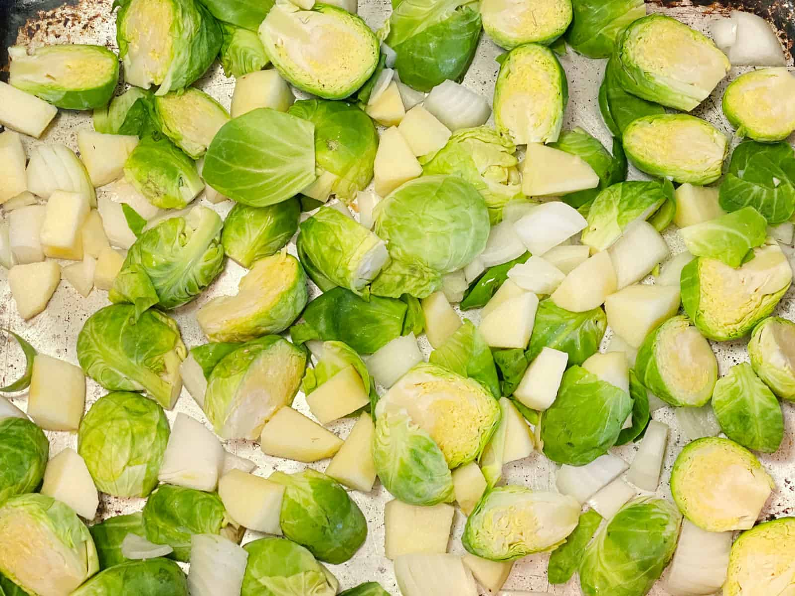 Brussels sprouts, onions, and apples chopped in a pan
