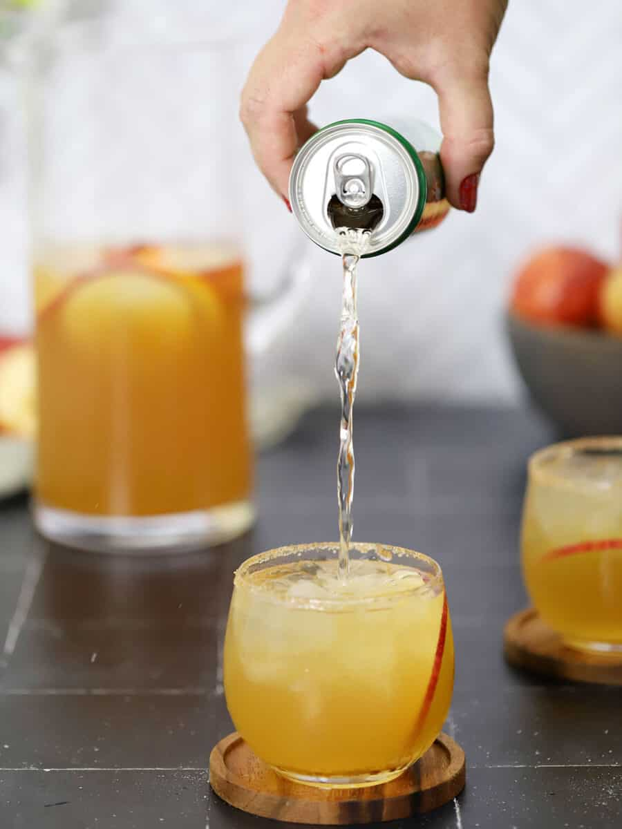 Pouring ginger ale into a glass of sangria