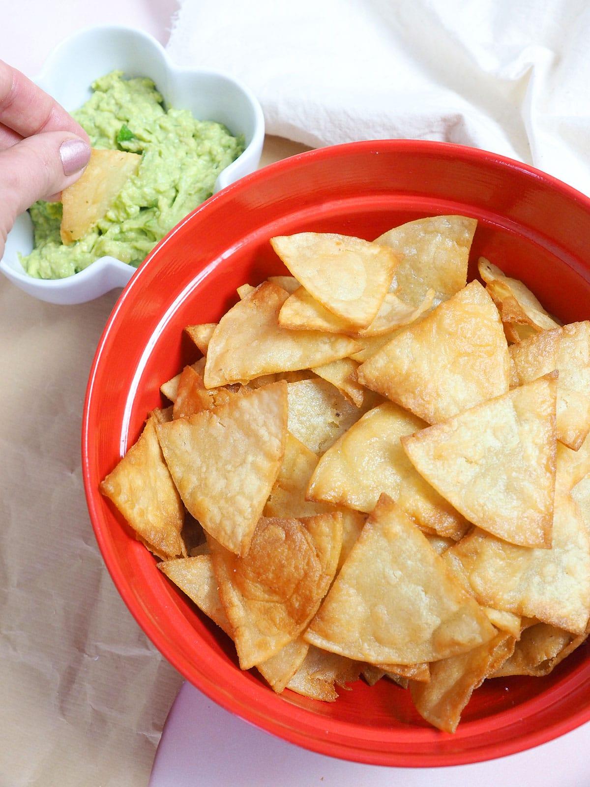 Red bowl full of homemade tortilla chips.