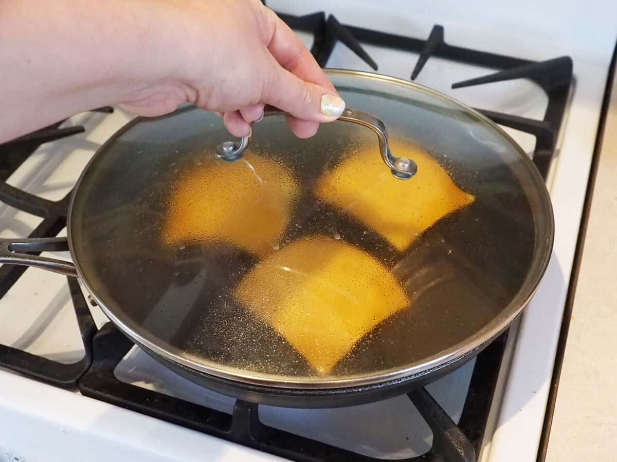 Placing a lid on a skillet of hamburger patties with cheese