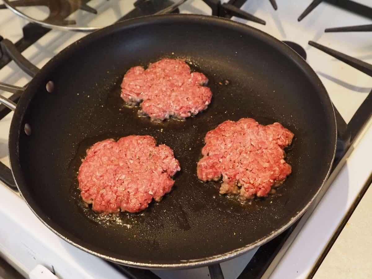 Raw hamburger patties in a skillet