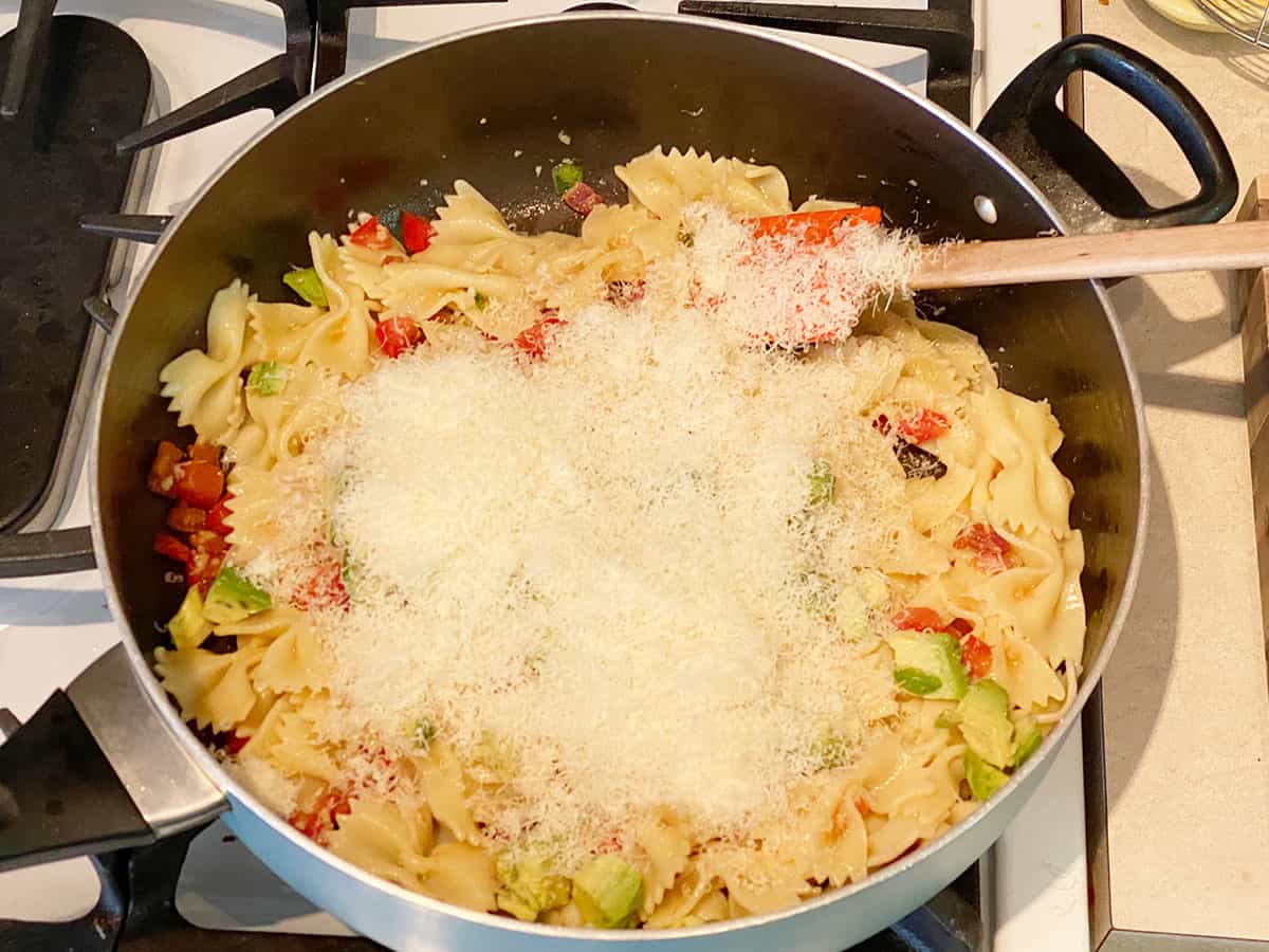 Freshly grated Parmesan cheese on top of a pan full of bacon avocado pasta.