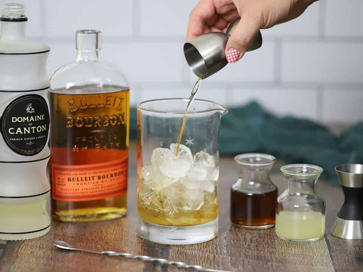 Pouring bourbon into a mixing glass full of ice