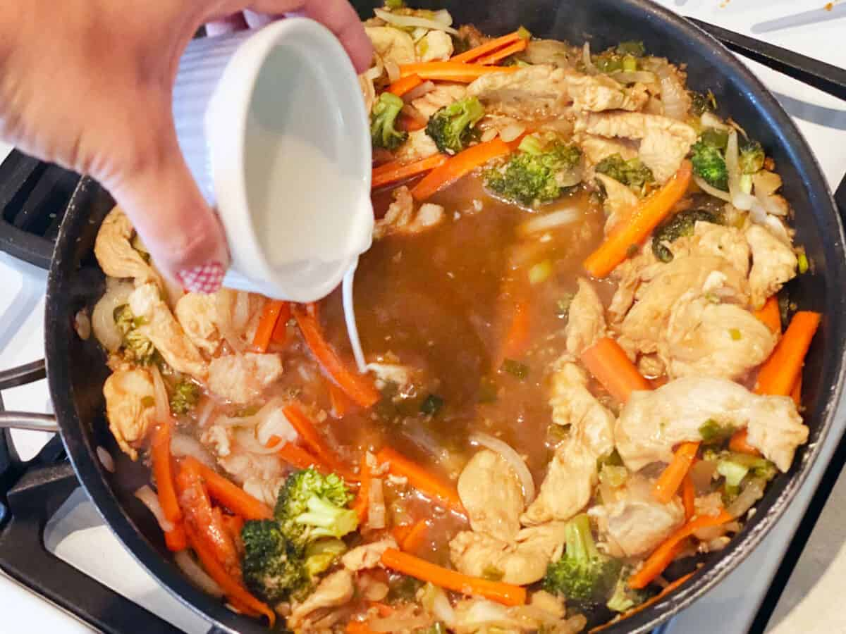 Cornstarch slurry being poured into a pan of meat and veggies.