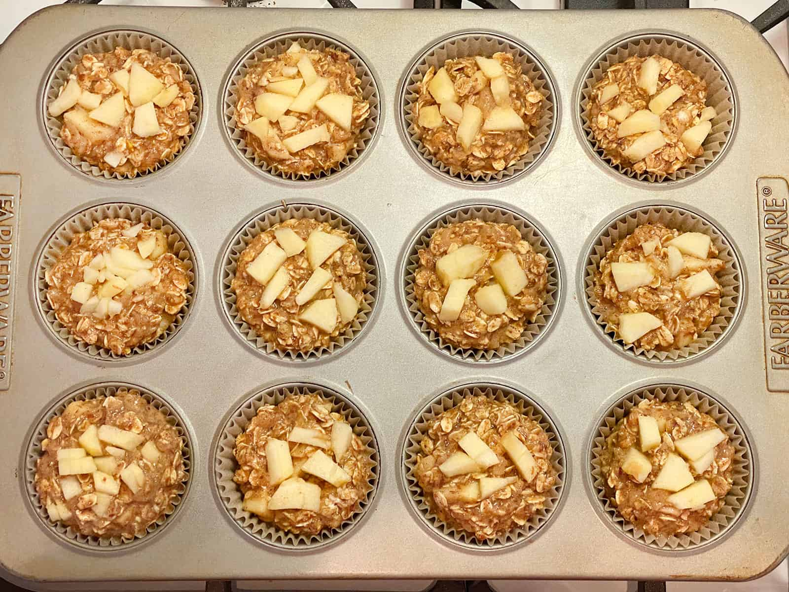 Apple Cinnamon Baked Oatmeal in muffin tins ready to go into the oven.