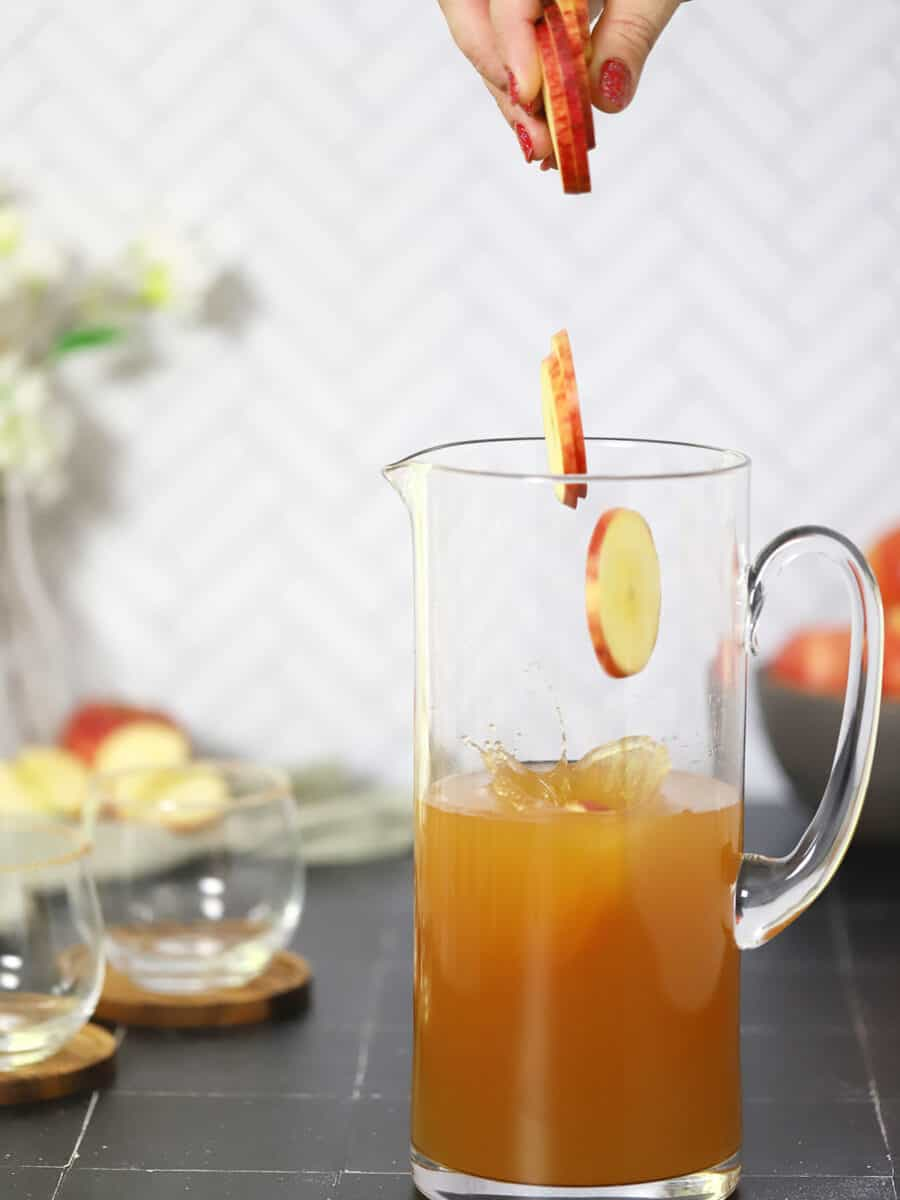 Apple slices falling into a pitcher of apple cider sangria