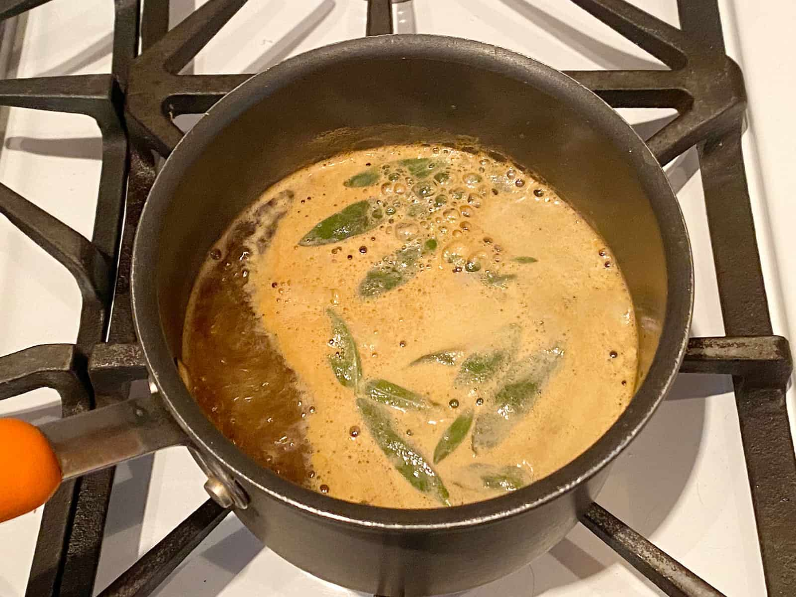 Apple cider, brown sugar, and sage simmering in a pot.
