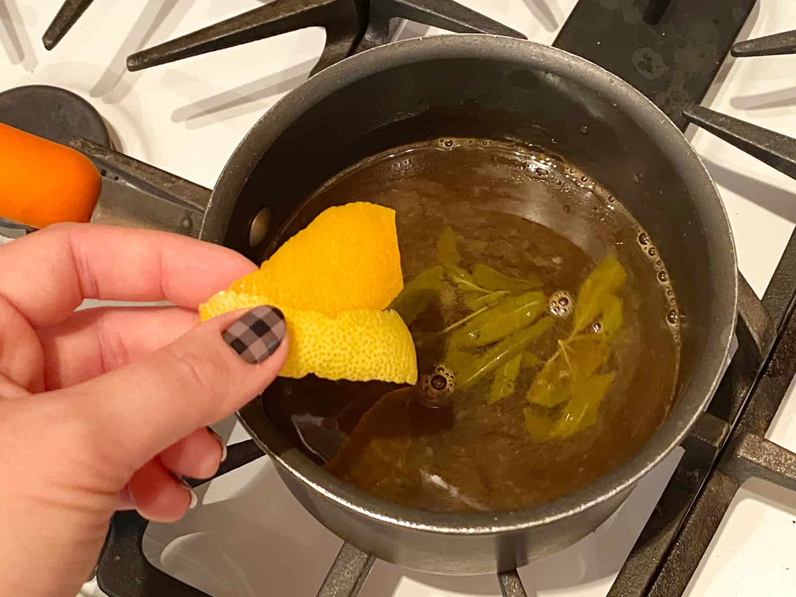 Orange peel and lemon peel being added to a pot on the stove.