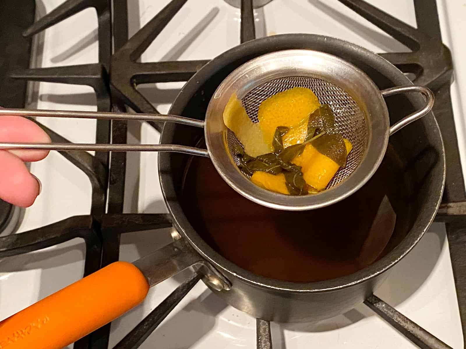Straining sage leaves and citrus peel from apple cider syrup
