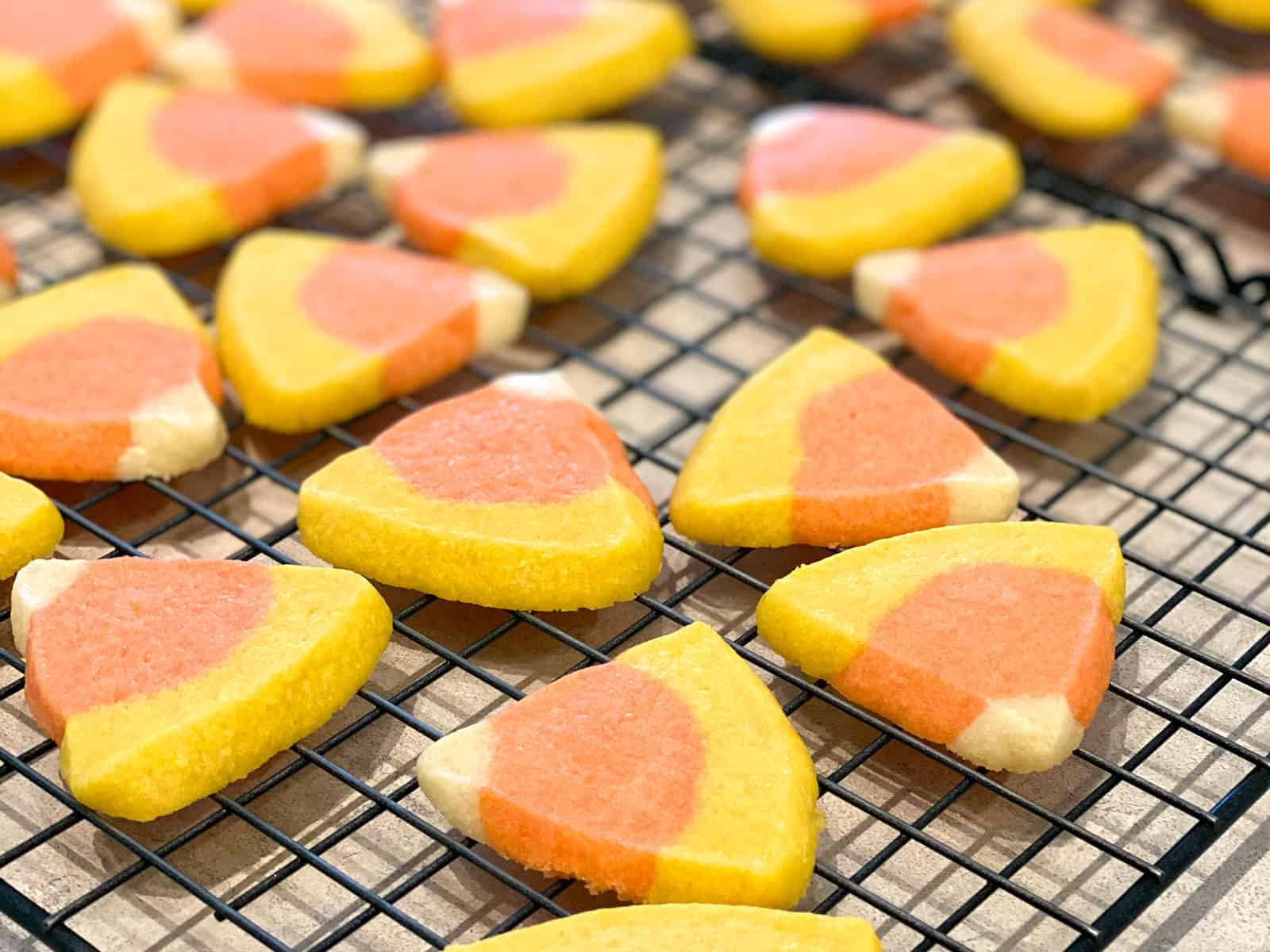 Candy corn shortbread cookies cooling on a wire rack