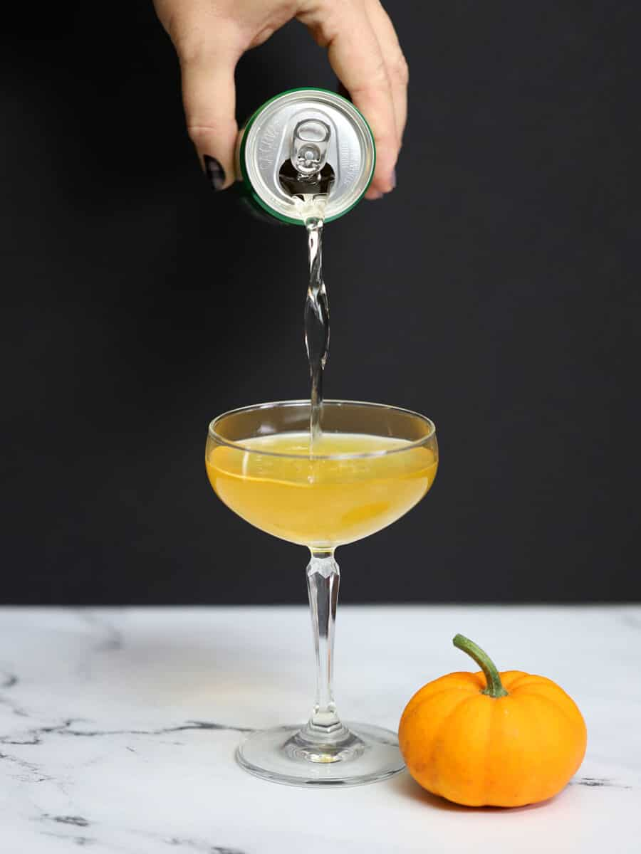 Ginger ale pouring in to a Pumpkin Ginger Martini