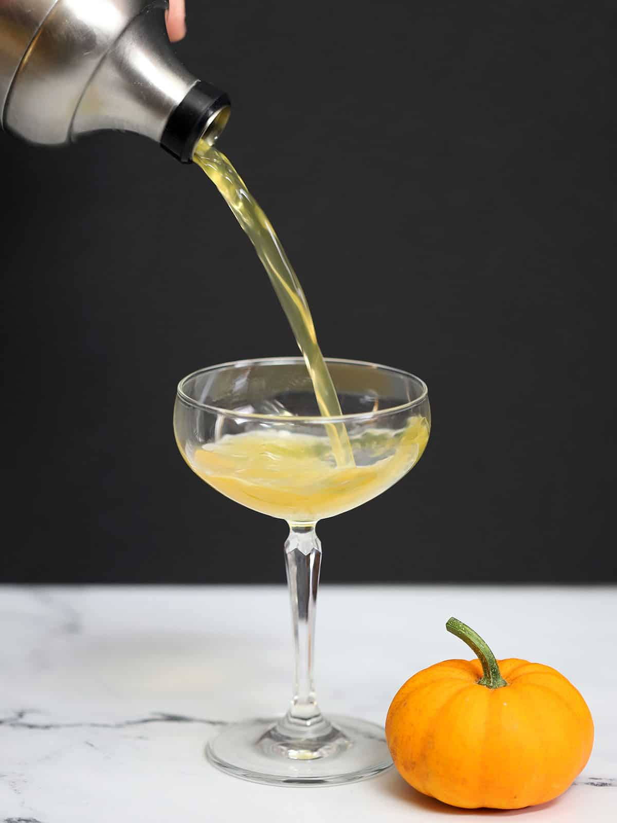 Pumpkin Ginger Martini being poured from a cocktail shaker into a glass.