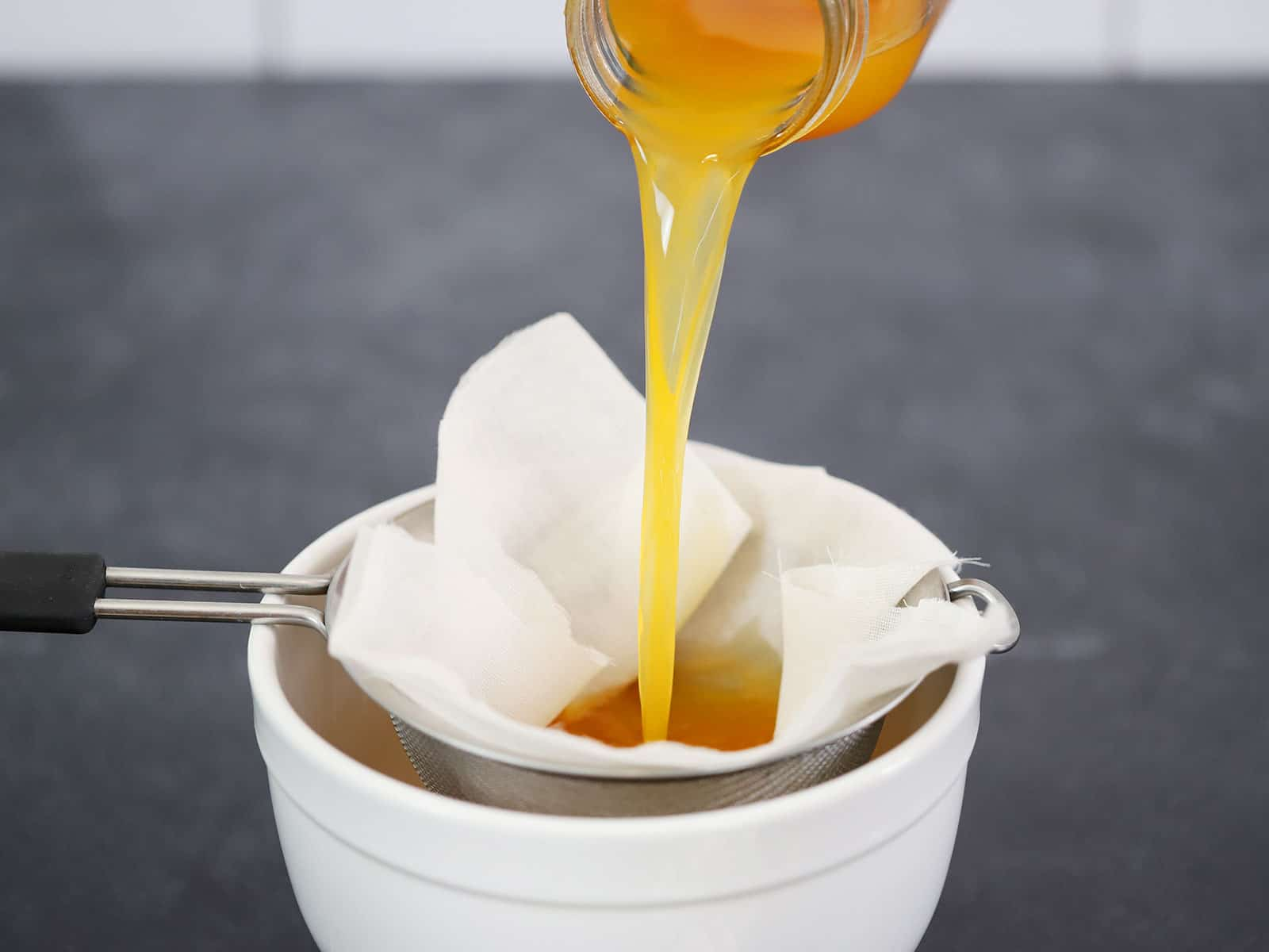 Pouring pumpkin vodka through cheesecloth
