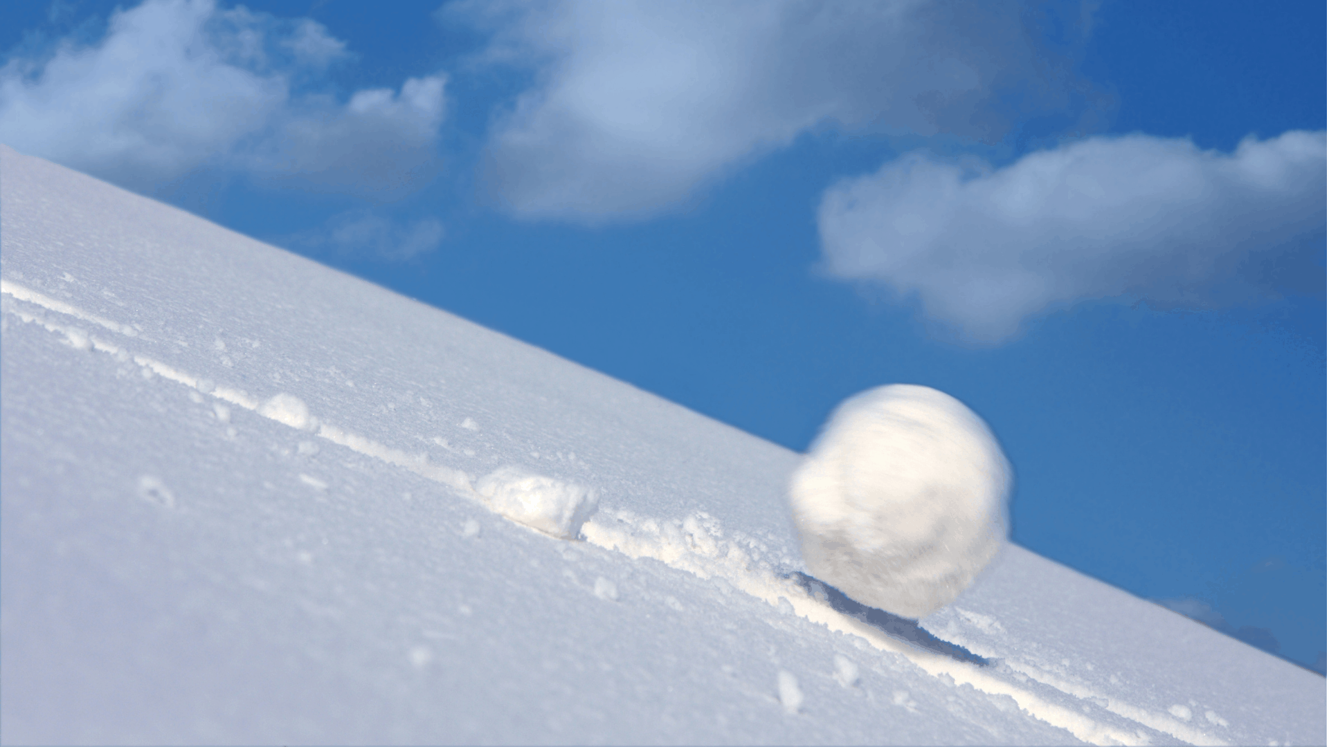 Snowball rolling quickly down a hill